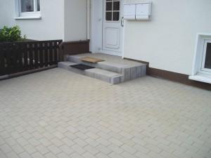 Der neue Eingang zum Haus. Gestaltet mit Betonpalisaden und Betonblockstufen. Der Parkplatz mit Betonrechteckpflaster