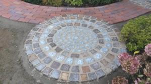 Natursteinelement in einem Klinkerweg. Für den Kreis verwendeten wir Porphyr und Granitpflaster